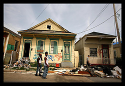 26 July 2006 - New Orleans - Louisiana. Young men walk past derelict buildings in the midtown part of the city. Much needs to be done to repair the ruined neighbourhoods where crime has started to take hold as youth returns to the city. The Louisiana National Guard have started to patrol the tough, thinly populated areas which NOPD is unable to handle on its own.