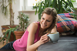 Young woman drinking coffee in living room and smiling, Munich, Bavaria, Germany