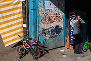 A man stands in the shadows by a doorway surrounded by childrens bicycles. Addis Ababa, Ethiopia.