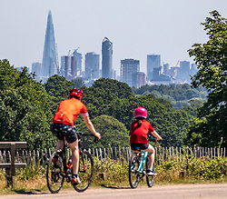 © Licensed to London News Pictures. 25/06/2020. London, UK. Cyclists out in Richmond Park where clear views of central London can be seen from the park in South West London as forecasters predict the hottest day of the year with temperatures expected to reach 33c with a warning that UV light is much stronger than usual due to lack of aircraft in the skies. Prime Minister, Boris Johnson announces that tourism and hospitality including pubs, restaurants and campsites can now reopen from the 4th of July as well as reducing the 2 metre rule to 1 metre.  Photo credit: Alex Lentati/LNP