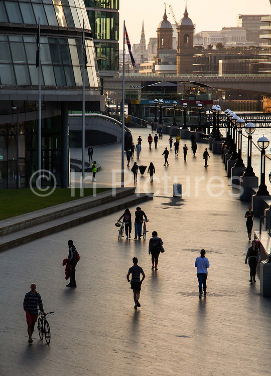 Joggers keeping fit while practicing social distancing during the lockdown by City Hall at 6pm on 9th April 2020 in London, United Kingdom. Normally crowded with people leaving work the City of London is like a ghost town as workers stay home during the Coronavirus pandemic.