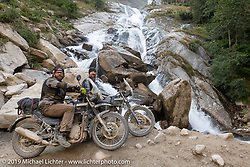 Tattoo artist Justin Big Meas Wilson and Led Sled's Pat Patterson on their Royal Enfield Himalayans at a roadside waterfall on the Motorcycle Sherpa's Ride to the Heavens motorcycle adventure in the Himalayas of Nepal. On the fifth day of riding, we went from Muktinath to Tatopani. Friday, November 8, 2019. Photography ©2019 Michael Lichter.