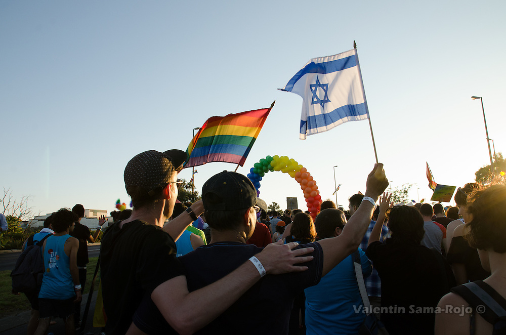Two men weaving a rainbow flag and an Israel flag.