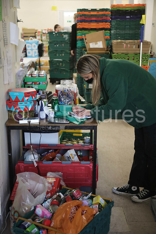 Workers and volunteers at Hackney Foodbank receive and organize food donations, 15th of December 2021, Hackney, East London, United Kingdom. Food donated is weighed in and registrered. The Hackney Food Bank is part of a nationwide network of foodbanks, supported by The Trussell Trust, working to combat poverty and hunger across the UK. The food bank gives out three days emergency food supplies to families and individual who go hungry in the borrough. The food is all donated by individuals and the food donated is held in a small ware house where it is  sorted and packed for distribution.  More people than ever in Britain have turned to the food bank for help and in Hackney the need has gone up with 350% over the past two years.