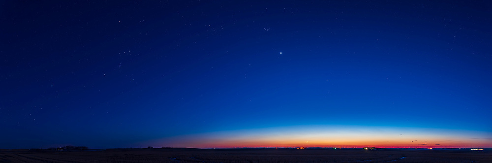 This is a panorama of the evening sky on March 25, 2020, with brilliant Venus high in the west at centre just after the date (March 24) of its greatest elongation in the evening sky for 2020. It appears here about as high as it can get with the ecliptic tipped up to a high angle in spring. To the left is Orion and the winter stars in the twilight, including Sirius at far left.  Just above the horizon right of centre in the bright twilight is the day-old thin crescent Moon about to set. Above Venus are the Pleiades and Hyades star clusters. <br /> <br /> This is a panorama of 5 segments with the Nikon D750 and 24mm Sigma lens, stitched with PTGui.  Each segment was 8 seconds at ISO 400 and f/2.8.