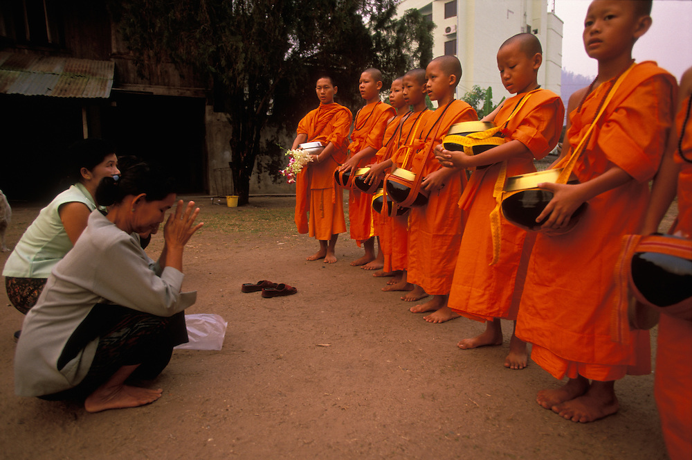 Two women greet novice monks with reverence when offering them food early in the morning, Mae Hong Son, Thailand.