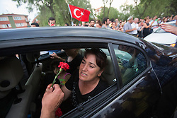 © licensed to London News Pictures. Eskisehir/TURKEY 10/07/2013. Emel Korkmaz, mother of Ali Ismail Korkmaz,19-year-old university student who was killed by Turkish riot police whilst supporting an anti-government demonstration, being given a carnation flower by a mourner at Ali's funeral procession in Eskisehir, Turkey. Ali suffered brain injury for more 38 days until he die and he has become the 5th protester who died in the recent demonstrations in Turkey which started with Istanbul's Gezi Park movement. Photo credit: Tolga Akmen/LNP