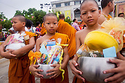 13 APRIL 2013 - BANGKOK, THAILAND: Thai novice monks hold their overflowing alms bowls after a merit making ceremony at Bangkok City Hall for Songkran. Songkran is the traditional Thai New Year's Festival. It is held April 13-16. Many Thais mark the holiday by going to temples and making merit by giving extra alms to monks or offering extra prayers. They also mark Songkran with joyous water fights. Songkran has been a national holiday since 1940, when Thailand moved the first day of the year to January 1.     PHOTO BY JACK KURTZ