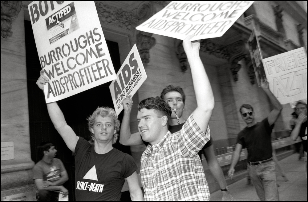 """On September 14th, 1989, ACT UP protested outside the New York Stock Exchange. Inside seven ACT UP members had infiltrated the Stock Exchange, chained themselves to the VIP balcony, unfurled a banner above the trading floor demanding """"SELL WELLCOME"""", and stopped trading on the floor.  Four days later, Burroughs Wellcome lowers the price of AZT by 20%, to $6,400 per year."""