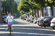 Een jongen fietst door Eijsden.<br /> <br /> A boy cycles through Eijsden.