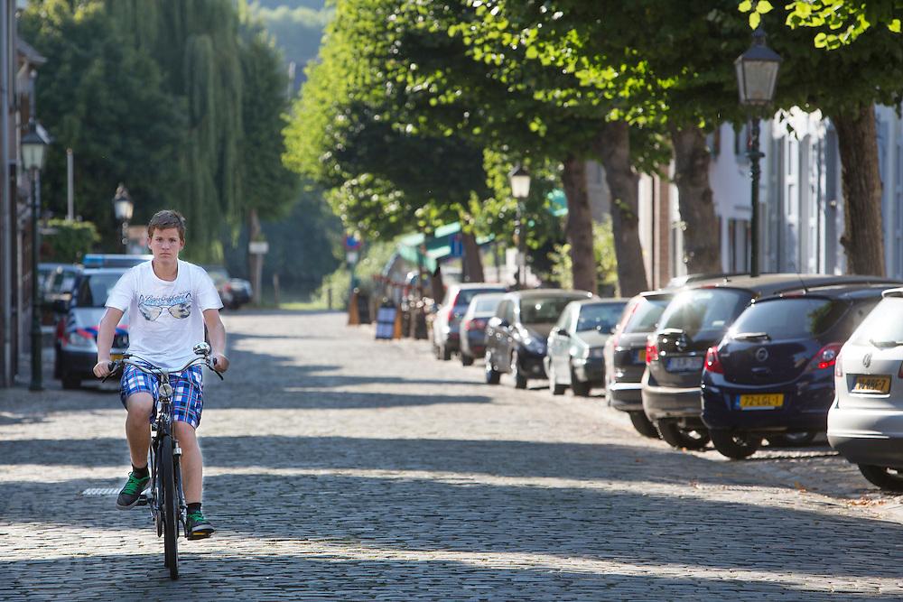 Een jongen fietst door Eijsden.<br /> <br /> A boy cycles through Eijsden.