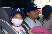 Youngsters react at the Dodger Day Drive-Thru at Belvedere Park, Tuesday, June 30, 2020, in Los Angeles. The event was hosted by The Los Angeles Dodgers Foundation, which distributed food boxes, books, sports equipment, clothing, toys and hygiene supplies to more than 1,000 registered youth from the Boyle Heights, East Los Angeles, La Puente and Monterey Park communities.