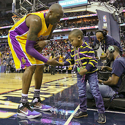 Feb 4, 2016; New Orleans, LA, USA; Los Angeles Lakers forward Kobe Bryant (24) meets three year old Jacoby Jones Jr during a timeout in the second half of a game against the New Orleans Pelicans at the Smoothie King Center. The Lakers defeated the Pelicans 99-96. Mandatory Credit: Derick E. Hingle-USA TODAY Sports