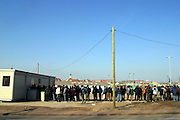 On an industrial wasteland in Calais, France refugees and asylum seekers line up to receive food from the charity Secour Cathlique, who feed them 2 meals a day..After the Sangatte refugee camp closed down an average of 200 refugees lived on the streets of Calais, without food, money or accommodation, trying most nights to get to Britain.  There were many different nationalities, mainly Iraqi and Afghani, but also Sudanese, Palestinian and Turkish. 95% are male, aged between 16 and 50.