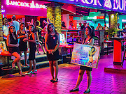 "03 NOVEMBER 2016 - BANGKOK, THAILAND:  Women who work at ""Bangkok Bunnies,"" a bar in Nana Plaza, attired in black mourning clothes, try to attract customers into the bar. Bangkok's infamous nightlife has been scaled back during the mourning period for the late Bhumibol Adulyadej, King of Thailand. The revered King died on 13 October 2016 at age 88. The government declared a year of mourning. The government ordered Thailand's notorious adult entertainment districts to turn off their neon lights, dress employees in black and ensure that music can't be heard on the street in front of the venues for 30 days, the government said the entertainment venues could resume normal operations on 14 November.       PHOTO BY JACK KURTZ"