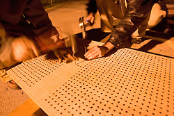 Stanford after dark. Stanford band members J.L. Podgurski, 2001 (L) and Zach Podell-Eberhardt, 2008 (R) build a bed of nails at a fraternity party. They had been working on it since 4 p.m.