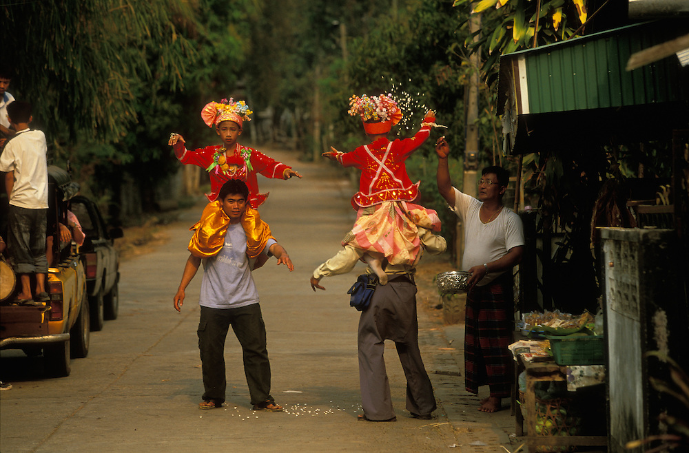 Attendants dance with boys dressed up as princes on their shoulders on their way to the house of some relatives during Poy Sang Long, the yearly ordination of novice monks, Mae Hong Son, Thailand. One of the relatives throws rice on them as a blessing.