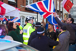 "Mayfair, London, November 28th 2014. A protest against Egypt's leader Al-Sisi descended into moinor scuffles as right wing ""patriots"" from anti-Islamic group Britain First arrived to protest against the presence of Islamist preacher Anjem Choudary, who was recently arrestred as part of an ant-terror operation. Playing patriotic British Music, Britain First accused Muslims of worshiping a ""devil"" and a ""paedophile prophet"". Police had to intervene before hotheads on both sides became violent. PICTURED: A Muslim Activist grabs a British flag from a Britain First protester inciting fury amongst the anti-Islamist group."