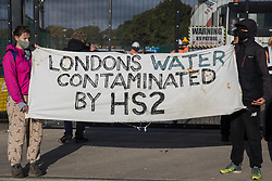 Environmental activists stand holding a banner in solidarity with HS2 Rebellion to block a gate providing access to a site for the HS2 high-speed rail link on 12 September 2020 in Harefield, United Kingdom. Anti-HS2 activists continue to try to prevent or delay works on the controversial £106bn HS2 high-speed rail link in the Colne Valley where thousands of trees have already been felled.