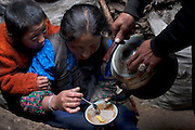 Nomadic herders Karsal and his wife Phurba pour butter tea onto their breakfast tsampa as their son watches at their home in the Tibetan Plateau.  (Karsal is featured in the book What I Eat: Around the World in 80 Diets.)