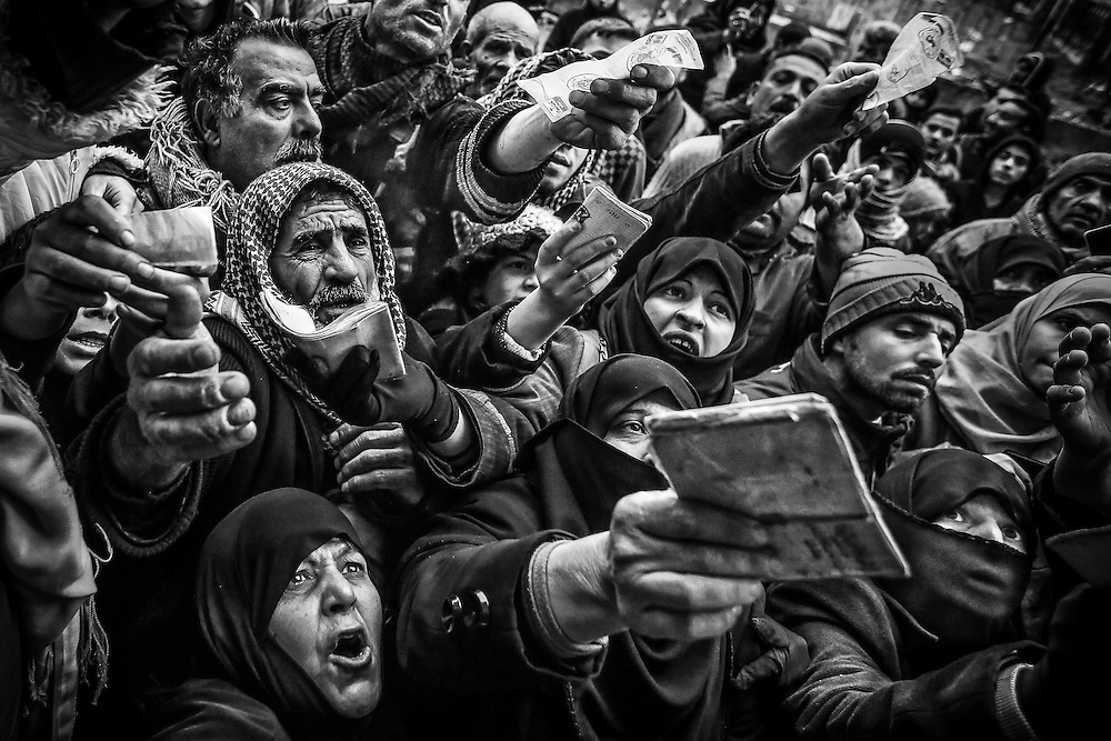 People rush and shout showing their IDs as the Free Syrian Army starts to distribute blankets.
