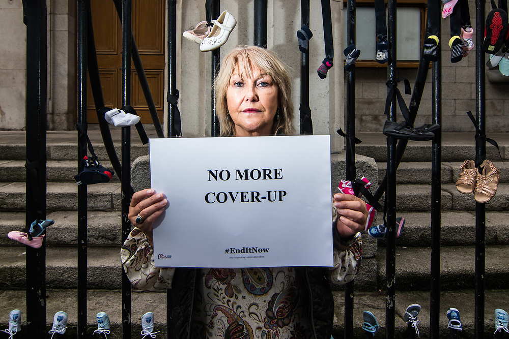 """Dublin, Ireland. 26th August, 2018. <br /> Margaret McGuckin, a northern Ireland survivor of child abuse by clergy, shows a banner that invite to stop the cover-ups by the vatican, in front of St. Mary Pro Cathedral, in Marlborough Street just ahead the Mass during the second of the two-days of the visit of Pope Francis in Dublin, Ireland.<br /> Pope Francis has made a two-day visit to the Republic of Ireland by celebrating a Mass at Dublin's Phoenix Park. The Argentine Pope asked forgiveness for the """"abuses in Ireland, abuses of power, conscience and sexual abuses"""" perpetrated by Church leaders. It was the first papal visit to Ireland for 39 years. During his activities many activists, victims and survivors have made protests and a silent march Garden of Remembrance towards the last Magdalene Laundry to close in Ireland.<br />  © Simone Padovani"""