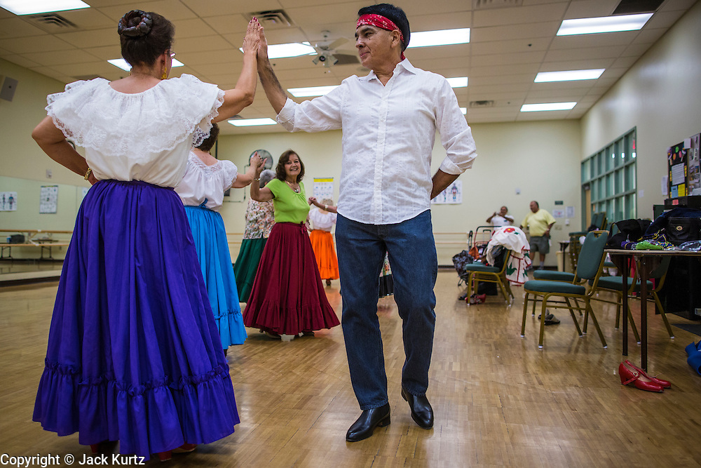 27 JUNE 2012 - GLENDALE, AZ:   MARGIE MAY, 65 years old, and HENRY ARBALLO dance during rehearsal for the Senior Fiesta Dancers at the Glendale Adult Center, in Glendale, AZ, a suburb of Phoenix. Dancing as a part of workout regimen is not unusual, but the Senior Fiesta Dancers use Mexican style folklorico dances for their workouts. The Senior Fiesta Dancers have been performing together for 15 years. They get together every week for rehearsals and perform at nursing homes and retirement centers in the Phoenix area once a month or so. Their energetic Mexican folklorico dances keep them limber and provide a cardio workout.  PHOTO BY JACK KURTZ