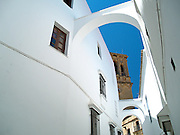 The church of Santa Maria and an alleyway spanned by three arches. Arcos de la Frontera, Spain.