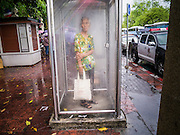 05 MAY 2013 - BANGKOK, THAILAND:  A Thai woman stands in a disused phone booth during an unseasonal thunderstorm near the Grand Palace in Bangkok, Thailand. The rainy season in Bangkok is usually mid June through early November, but 2013 has seen unseasonal rains through what is normally Bangkok's dry season.       PHOTO BY JACK KURTZ