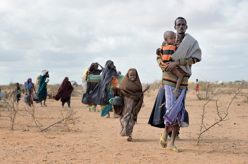 """Newly arrived refugees carry their belongings through the Dadaab camp in northeastern Kenya in 2011. Long the world's world's largest refugee settlement, Dadaab swelled with tens of thousands of new arrivals fleeing drought in Somalia. Under """"informed consent"""" rules that require prior approval, the photographer would have had to stop the tired family, explain the intricacies of usage and consent, then get their signatures on the paperwork before allowing them to continue their trek across the hot desert. Photo by Paul Jeffrey."""