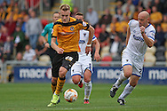 Joe Pigott of Newport (left) takes on Barry Fuller of Wimbledon. Skybet football league two match, Newport county v AFC Wimbledon at Rodney Parade in Newport, South Wales on Saturday 27th Sept 2014<br /> pic by Mark Hawkins, Andrew Orchard sports photography.