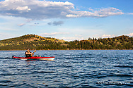 Logan Haney sea kayaking on Flathead Lake with Wild Horse Island State Park in background near Dayton, Montana, USA model released