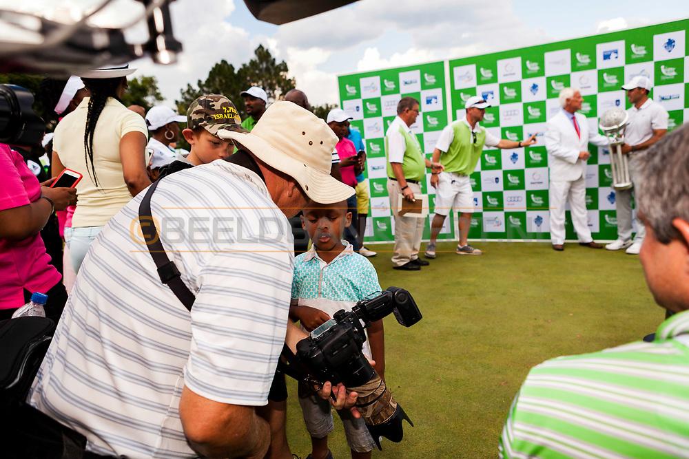 14-02-2016 -  Golffoto's: Tshwane Open 2016: jongetje vraagt fotograaf hoe alles werkt. Genomen tijdens het Tshwane Open South Africa 2016 op de Pretoria Country Club in Waterkloof, Zuid-Afrika.
