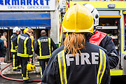 A female London Fire Brigade firefighter talks to the Sector Commander during an emergency response to an explosion on the basement of a shop in North London, United Kingdom. The London Fire Brigade is the 4th largest fire-service in the world.  As of 2012, there were 257 female firefighters in the London Fire Brigade.  As of March 2007, the proportion of operational firefighters in the UK who were women was 3.1%.