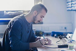 Young male technician soldering electronic components in an industrial plant, Freiburg im Breisgau, Baden-W¸rttemberg, Germany