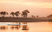 Silhouettes of small boats drifting on the calm water of the Bani River at Djenné, Mali