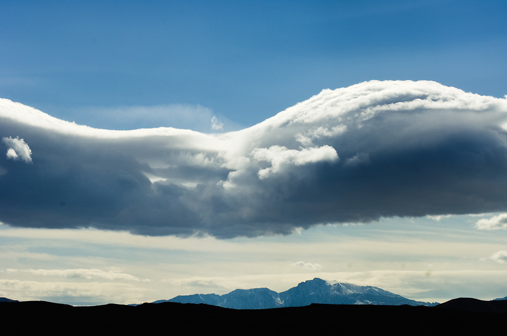 Lenticular clouds over the distant Sierra Nevada Range, afternoon light, April, view from Death Valley National Park, California, USA