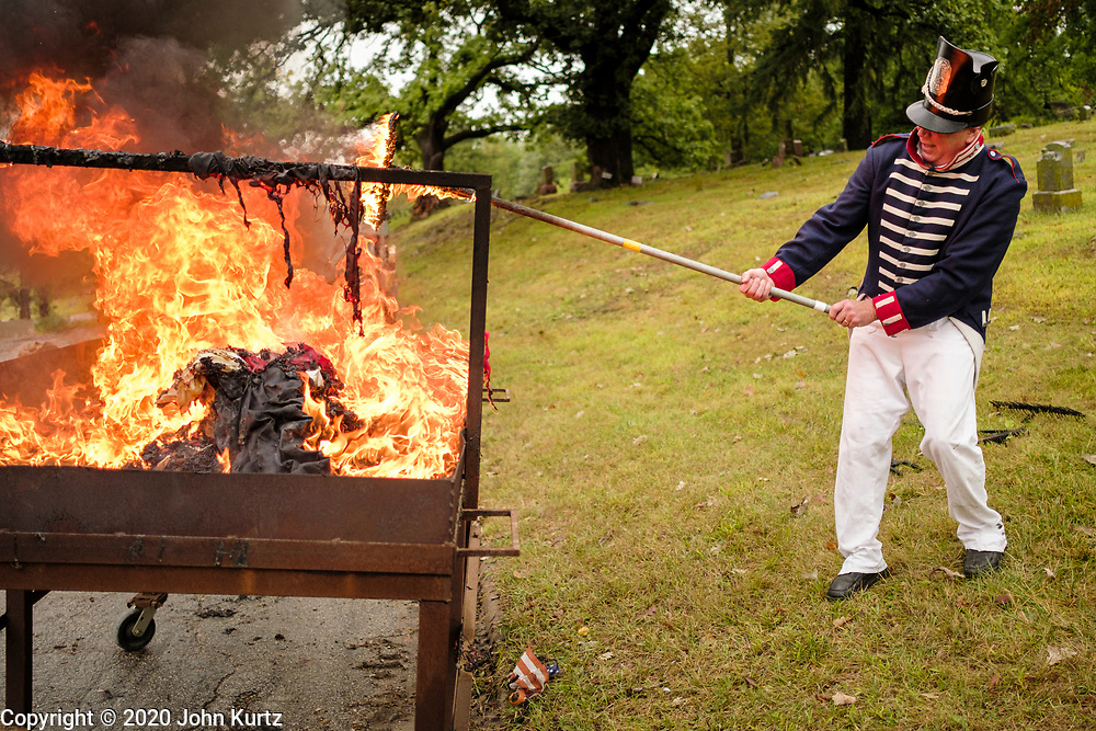 12 SEPTEMBER 2020 - DES MOINES, IOWA: MIKE ROWLEY, wearing a replica of a US Army uniform from the War of 1812, tends the fire during a flag retirement ceremony at Glendale Cemetery in Des Moines. About 10 volunteers came to the cemetery Saturday morning to properly dispose of about 4,000 American flags. The flags had flown over veterans' graves, local businesses, and state offices. The US Flag Code calls for used American flags to be respectfully disposed of in a fire.     PHOTO BY JACK KURTZ