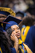 CSF-DC's Dalesa Harleston smiles as she talks with family on the phone during her NC A&T graduation on Saturday, May 14, 2016 (Tigermoth Creative/Chris English)