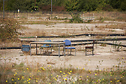 Office table and bucket chairs furniture on empty wasteland in an industrial estate, Northfleet, Thames Gateway