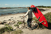 A surfer with a surfboard on his bicycle rack checks out the surf at Sakonnet Point in Little Compton, Rhode Island.