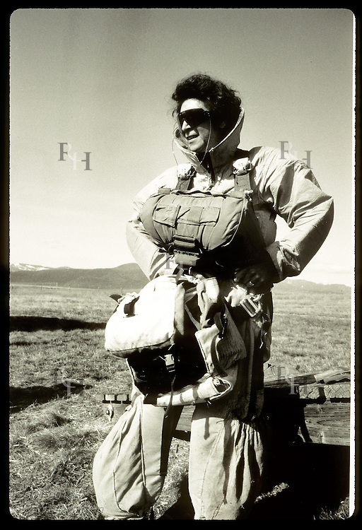 Female smokejumper in full jumpsuit carries personal gear bag she sewed herself; Missoula. Montana