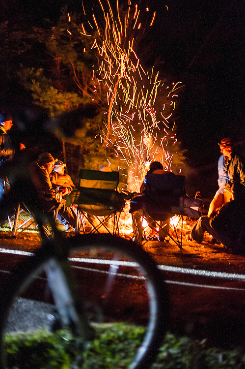 Mountain bikers finish a night ride around a campfire.