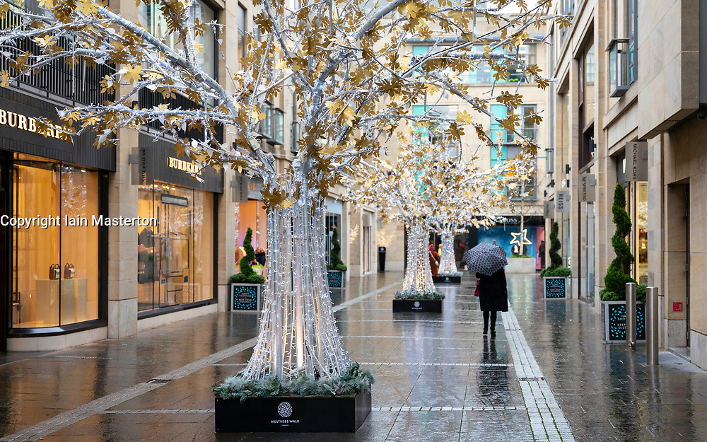 Edinburgh, Scotland, UK. 20 November 2020. Shop window displays with posters offering large discounted sale prices on Black Friday in Edinburgh. Pictured; Upmarket Multrees Avenue shopping precinct with Christmas decorations and lone shopper .Iain Masterton/Alamy Live News
