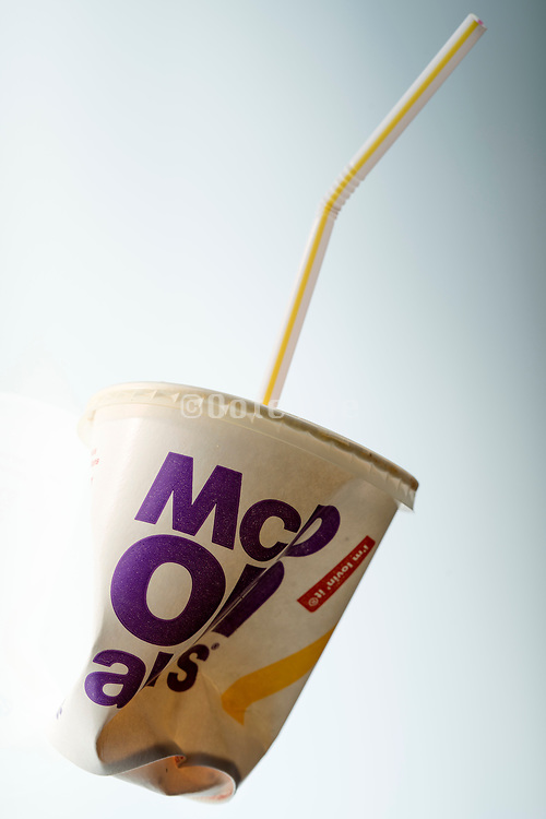 crushed McDonalds paper cup with plastic straw