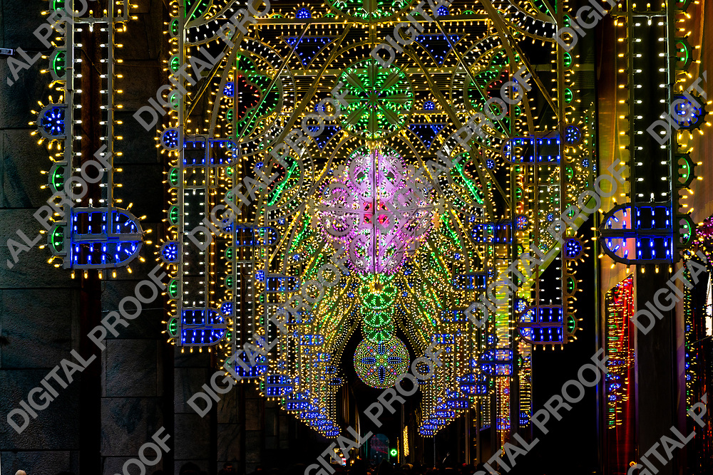 People walking in arched halls of Piazza del Duomo with glowing colorful decoration on Christmas Eve in Milan Italy
