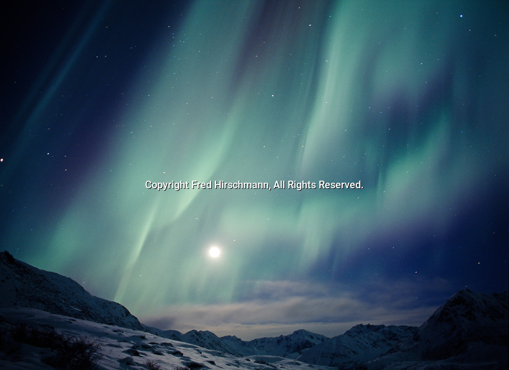 Aurora above the Talkeetna Mountains with rising moon, Little Susitna River Valley, early morning hours of December 27, 2002, Alaska.