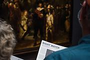 Buitenlandse toeristen bekijken het schilderij Nachtwacht in het Rijksmuseum