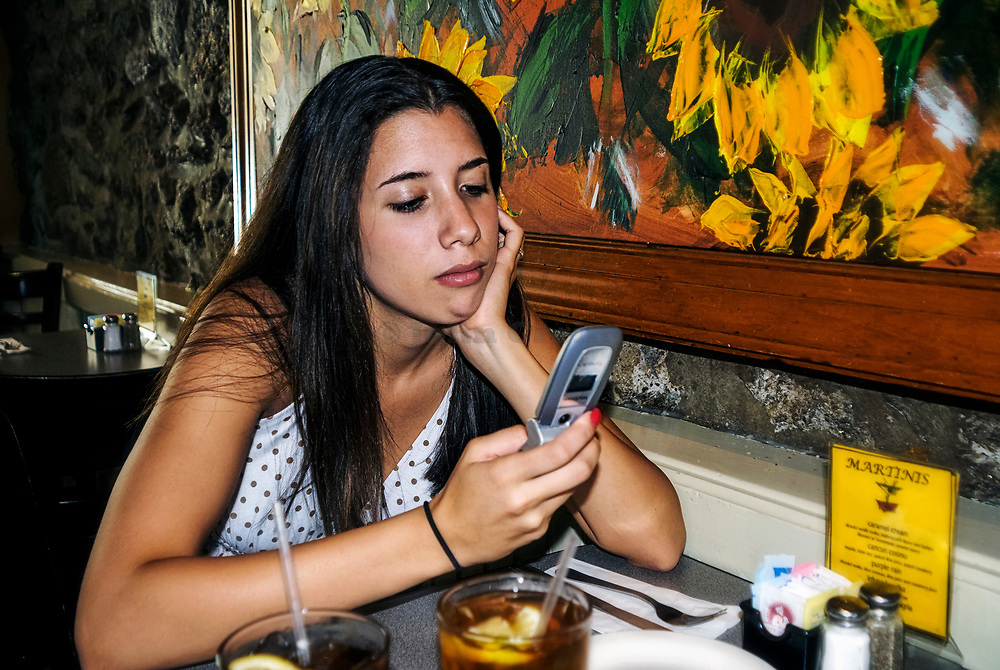 Teenage girl checks and sends text message while waiting in a restaurant.