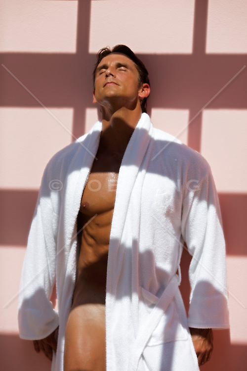 naked man with a white open bathrobe standing against a wall